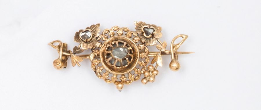 Broche en or jaune à décor floral, ornée de diamants taillés en rose. P. Brut :…