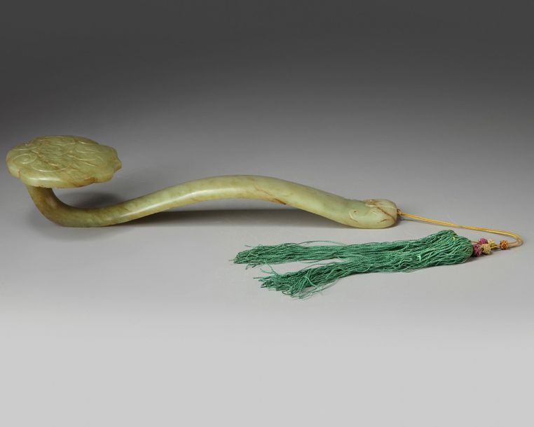 A Chinese celadon jade ruyi sceptre The head of the ruyi-sceptre is carved in relief…