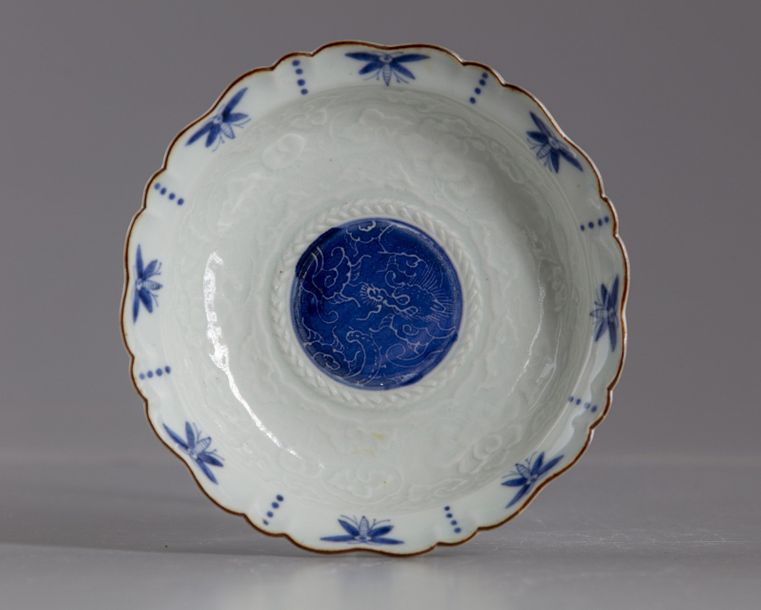 A Japanese blue and white dish A Japanese dish decorated in the center with a dragon,…