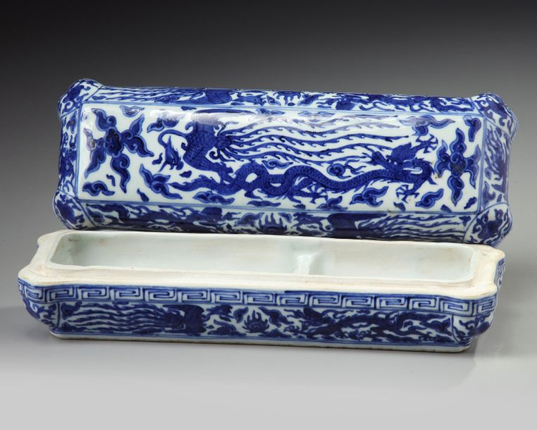 A Chinese blue and white 'dragon and phoenix' pen box The shaped elongated box is…