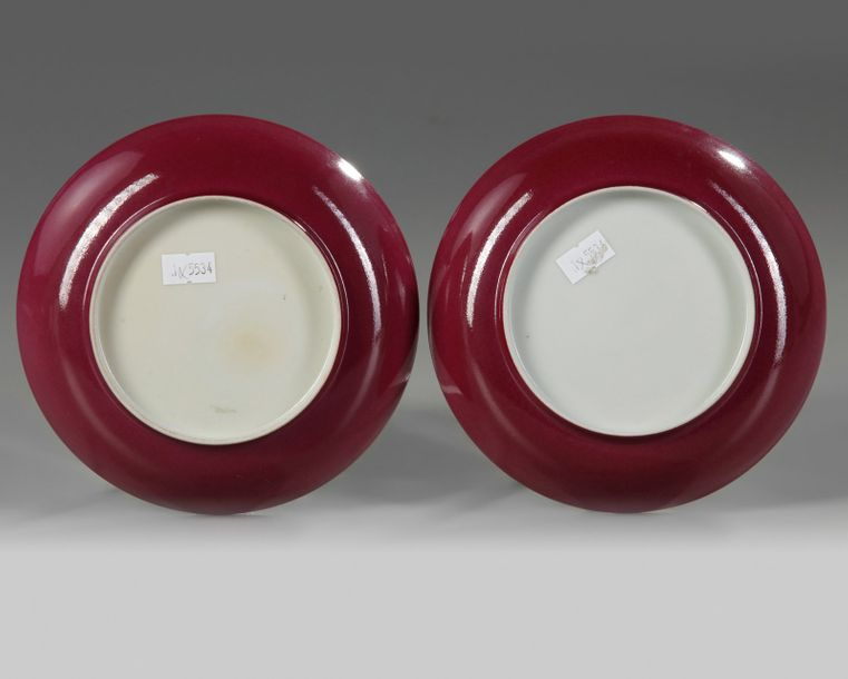 A pair of Chinese ruby-back famille rose 'lady and boys' dishes Each dish is decorated…