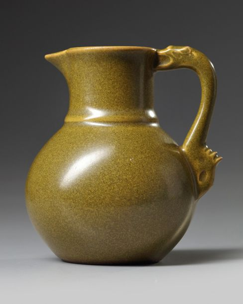 A Chinese teadust-glazed ewer The small vessel is decorated with a handle shaped…
