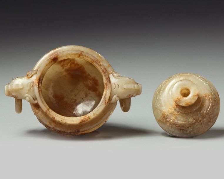 A Chinese russet jade tripod censer and cover The jade of a grayish and russet tone.…
