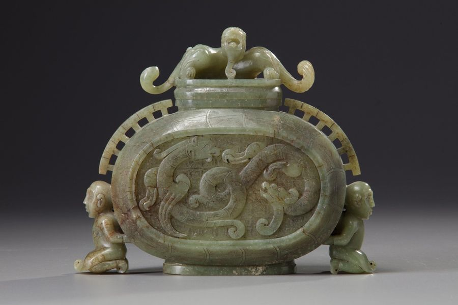 A Chinese celadon jade archaistic vase and cover The flattened vase with a round…
