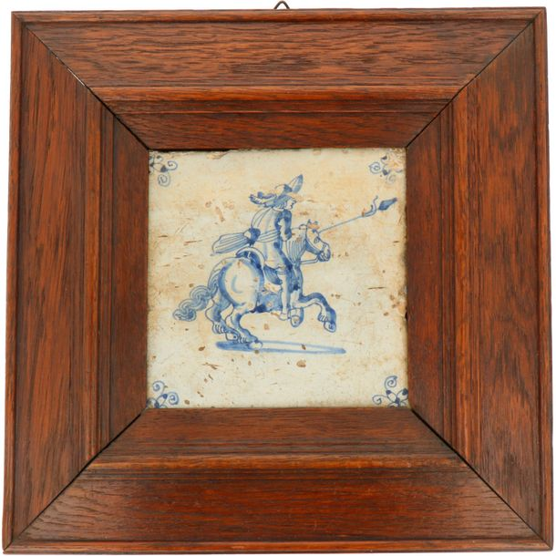 A lot of two earthenware tiles depicting a knight, in a wooden frame. Delft, 18th…