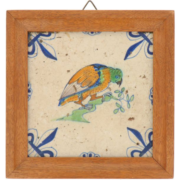A lot of three earthenware tiles with polychrome decor in a wooden frame. Delft,…
