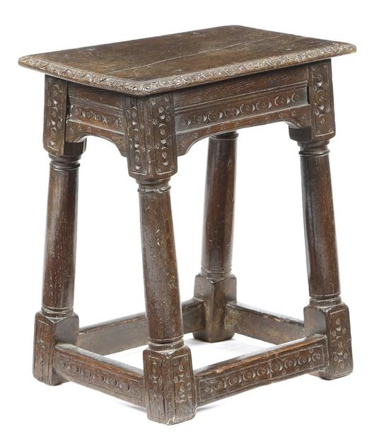 An oak joint stool, the seat with a carved edge, the frieze and legs with punched…
