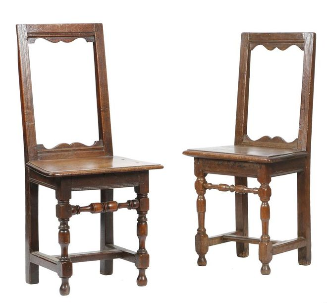 Two similar early 18th century oak backstools, each with an open back with arc d'arbelete…