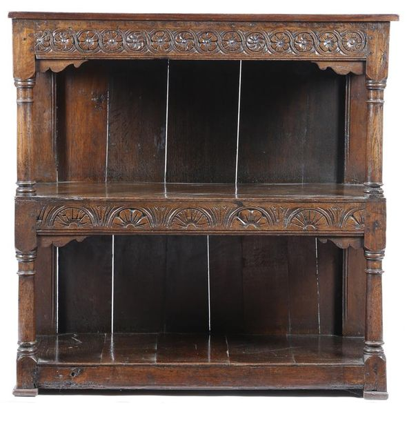 A 17th century and later oak three tier buffet, with flowerhead, guilloche and lunette…