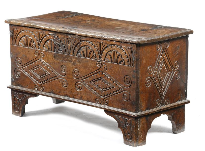 A carved oak coffer, the hinged lid revealing a vacant interior, above a frieze…