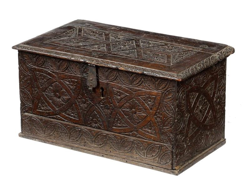 An early 17th century boarded oak box, with chip carved decoration of leaves, flowerheads…