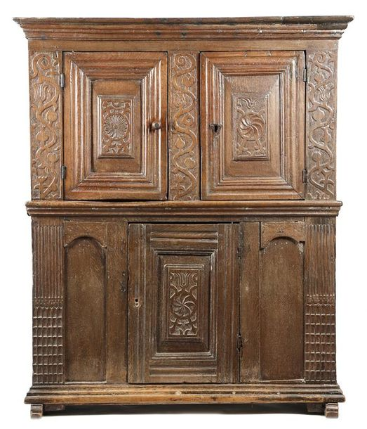 An oak cupboard, with two hinged doors with carved panels, one with a tulip and…
