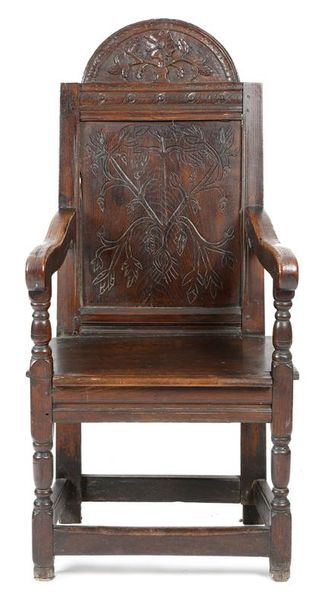 An oak panelled back armchair, the arched top carved with an urn issuing flowers…