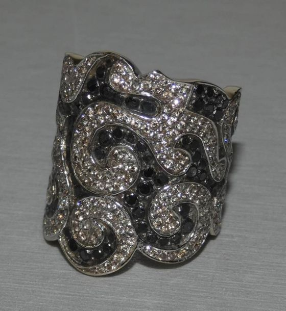 Importante bague en or gris pavée de diamants noirs et diamants blancs à décor de…