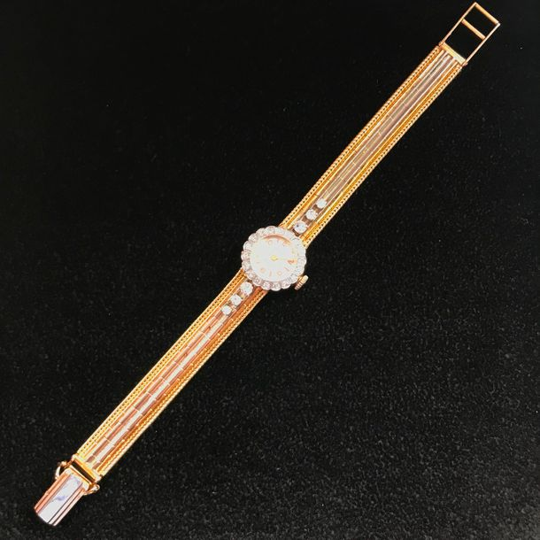 A yellow gold, platinum and diamond lady's wristwatch by EVIANIA. Cadran argent…